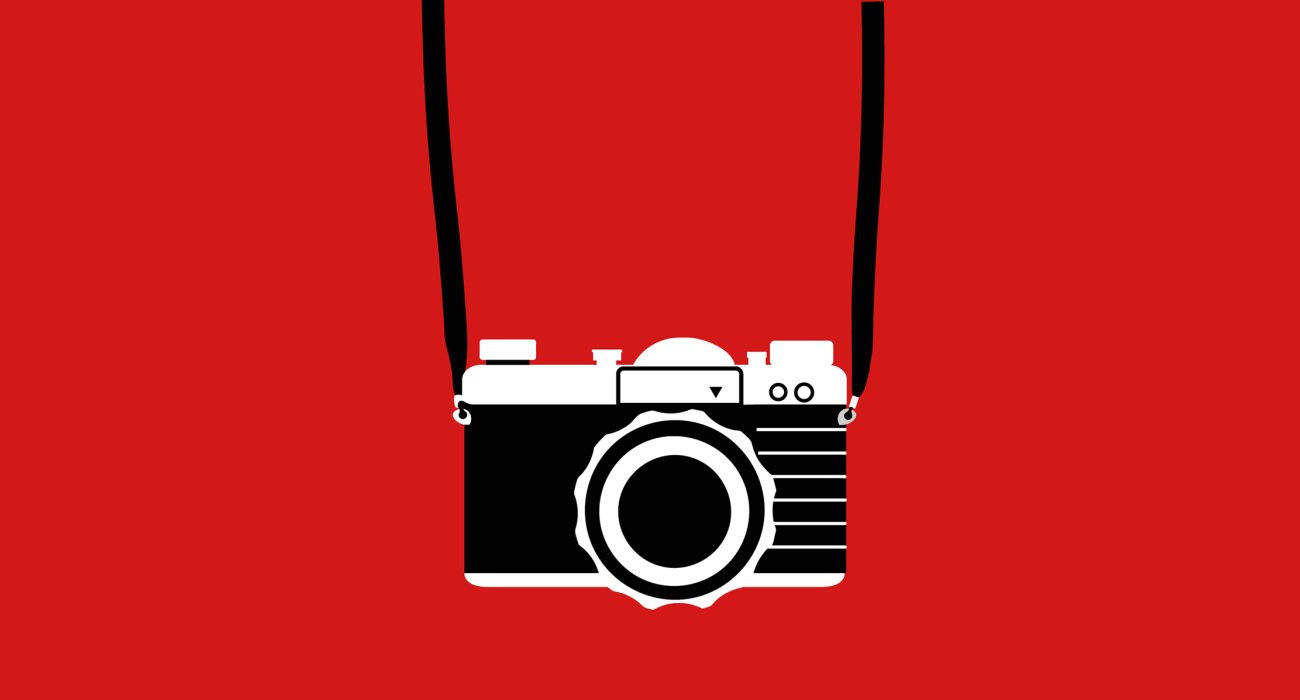 A simple line graphic of a 35mm camera hanging from a neckstrap and positioned as if it being worn by the wearer of the shirt. My god quite the optical illusion